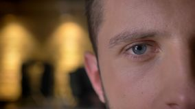 Closeup half-face front shoot of adult caucasian male eye looking at camera indoors with interior on the background stock photo