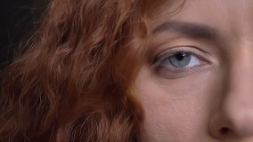 Closeup half-face portrait of adult caucasian red-haired face with blue eye looking straight at camera.  stock video footage
