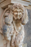 Closeup half naked faunus statue under column at Zwinger palace Stock Images