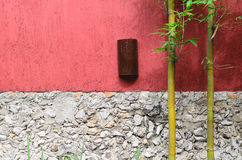 Closeup of half red half gray stone wall and two bamboo Royalty Free Stock Photography