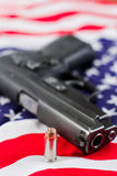 Second amendment concept. Closeup of a hallow point bullet with a gun and an American flag fading to a shallow depth of field Stock Photo