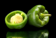 Closeup halved green bell peppers isolated on black Royalty Free Stock Photos