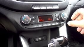 Closeup of hand adjusting the air conditioner button in the car. Man using automobile air conditioning system. Dual climate control in the car stock video
