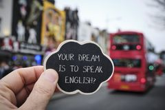 Text your dream is to speak English, in London, UK. Closeup of the hand of a caucasian man holding a black signboard with the question your dream is to speak royalty free stock photos