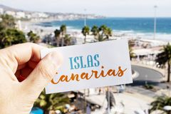Text Canary Islands in a signboard in Maspalomas. Closeup of the hand of a caucasian man holding a signboard with the text Islas Canarias, Canary Islands written royalty free stock image