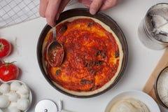 Closeup hand of chef adding tomato sauce on the pizza dough stock photos