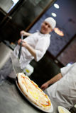 Closeup hand of chef baker in white uniform making pizza at kitchen Royalty Free Stock Photos
