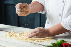 Closeup hand of chef baker in white uniform making pizza at kitchen. Or studio Royalty Free Stock Images