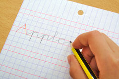 Closeup of the hand of a child writing apple word Stock Photo