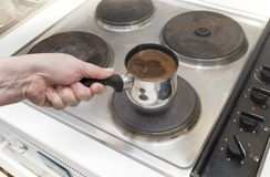Coffee about to boil over. Closeup of a hand and coffee about to boil over on the electric stove top stock photography