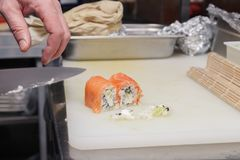 Closeup of the hand the cook cuts a philadelphia roll in a restaurant kitchen with sharp knife of sushi. Concept cooking Japanese stock images
