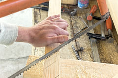 Closeup of hand cutting wood with a  hand saw Royalty Free Stock Image