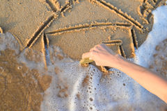 Closeup of hand drawing house on sand beside sea Royalty Free Stock Image