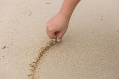 Closeup hand drawing or writing something on sand. Beach royalty free stock photo