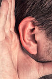 Closeup for hand on ear. Trying to hear something stock photography