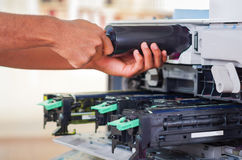 Closeup hand in front of open photocopier during maintenance repairs using handheld tool, black mechanical parts Royalty Free Stock Photo