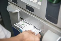 Closeup of a hand getting money from an ATM stock photo