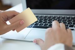 Closeup hand of girl typing credit card details on laptop to complete payment process. Shallow depth of field with focus. Closeup hand of girl typing credit card stock image