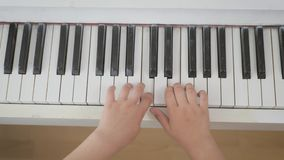 Closeup hand girls playing piano. Piano keyboard with hands. Top view on hand kids playing the piano. Favorite classical. Music stock video