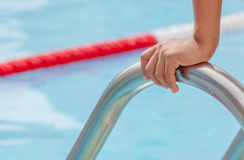 Closeup the hand grabs on the metallic bar of swimming pool, rea Stock Photos