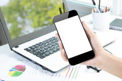 Closeup hand hold smartphone and laptop on desk background Stock Photo