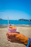 Closeup of hand holding cebiche with beach Royalty Free Stock Images