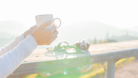 Closeup the hand holding a cup of coffee; light and lens flare e Royalty Free Stock Photography