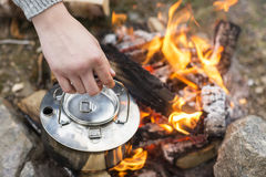 Closeup Of Hand Holding Kettle Over Bonfire Royalty Free Stock Image