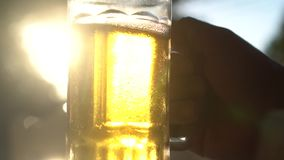 Closeup hand holding lager beer mug with sun rays. Closeup hand holding fresh lager beer mugs with sun rays in hot summer day- video in slow motion stock video