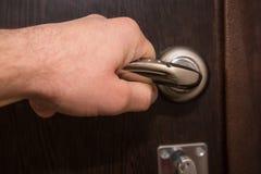 Closeup of hand holding metal silver doorknob Stock Photography