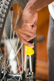 Closeup hand holding multi screwdriver working on mechanical parts next to wheel spokes Royalty Free Stock Photos