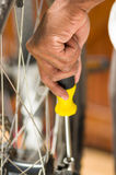 Closeup hand holding multi screwdriver working on mechanical parts next to wheel spokes Royalty Free Stock Images