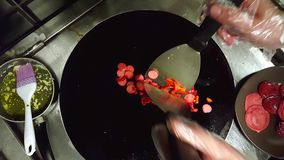 Cook frying sliced sausages with red peppers on a black cooker. Closeup of a hand with hygienic gloves holding tong and frying sliced sausages with red peppers stock video footage