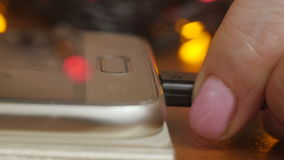 Closeup of a hand includes exercises. Closeup of the hands of a man plugging in the plug of his smpartphone in a socket, with a filter effect stock video footage