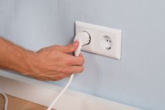 Closeup of hand inserting an electrical plug Stock Images