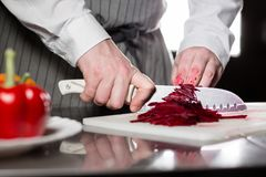 Closeup of hand with knife cutting fresh vegetable. Young chef cutting beet on a white cutting board closeup. Cooking in Stock Photo