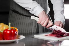 Closeup of hand with knife cutting fresh vegetable. Young chef cutting beet on a white cutting board closeup. Cooking in Stock Photography