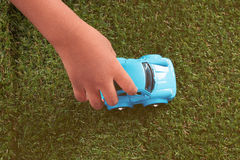 Closeup of hand little boy playing blue toy car on green grass Stock Images