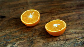 Closeup of hand of man cutting an orange on wooden table stock video