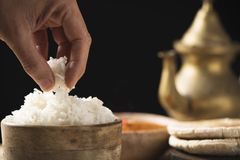 Rice and chicken korma. Closeup of the hand of a man having some cooked rice from a bowl placed on an off-white wooden table, next to a bowl with a chicken korma royalty free stock photos
