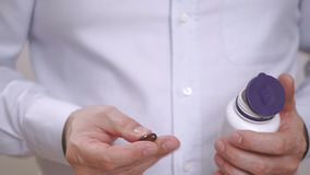 Closeup of the hand of a man pulling out an Omega 3 capsule. Closeup of the hand of a man pulling a brown Omega 3 capsule out of a container stock video