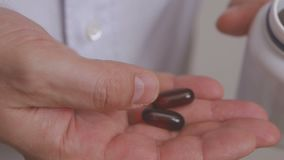 Closeup of the hand of a man pulling out an Omega 3 capsule. Closeup of the hand of a man pulling a brown Omega 3 capsule out of a container stock video footage