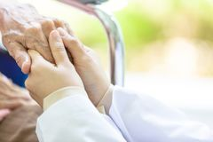 Closeup of hand medical female doctor or nurse holding senior patient hands and comforting her,.Caring caregiver woman supporting stock photography
