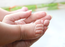 Closeup hand of mother holding baby foot stock photography