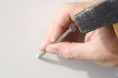 Closeup hand with nail and hammer at wall Royalty Free Stock Photo