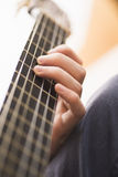 Closeup of hand and neck of acoustic guitar Stock Images