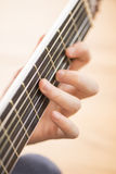 Closeup of hand and neck of acoustic guitar Stock Photos