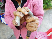Closeup hand of an old asian female pensioner on a walking stick Stock Image
