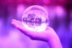 Closeup of hand holding a glass sphere with reflection of trees. Closeup of hand outdoors holding a glass sphere with reflection of trees Royalty Free Stock Image