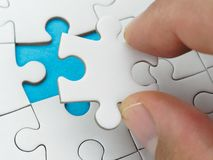 Closeup hand placing last piece puzzle. Closeup hand placing last piece of puzzle royalty free stock photo